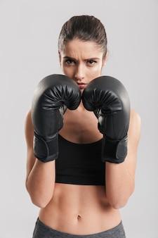 Foto van mooie donkerbruine sportvrouw opleiding in bokshandschoenen en het kijken, over witte muur