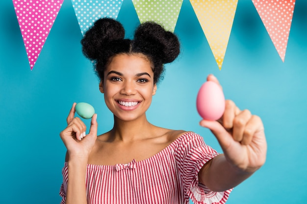 Foto van mooie donkere huid dame houden vakantie beschilderde eieren kleurrijk decor vlaggen goed humeur familie bijeenkomst diner slijtage rood wit gestreept shirt naakte schouders geïsoleerde blauwe kleur muur