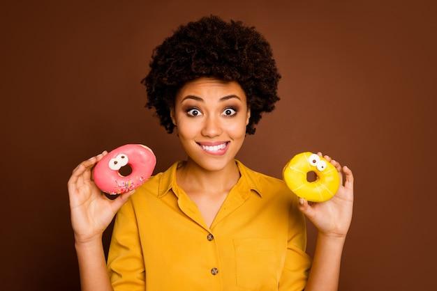 Foto van mooie donkere huid dame houdt twee kleurrijke donuts karamel ogen menselijke gezichten schilderen zorgeloos verlangen hongerig bijten lippen dragen geel shirt geïsoleerde bruine kleur
