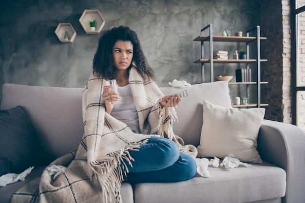 Foto van mooie donkere huid golvende dame houdt pijnstillers waterglas lijden griep gevangen koud papieren servetten overal zittend bank bedekt plaid deken woonkamer binnenshuis