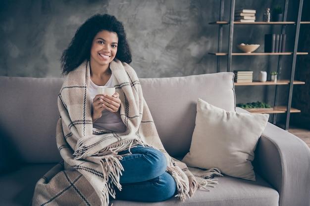 Foto van mooie donkere huid golvende dame warme koffie drinken beker genieten weekend thuis zitten gezellige bank casual outfit bedekt met deken woonkamer binnenshuis