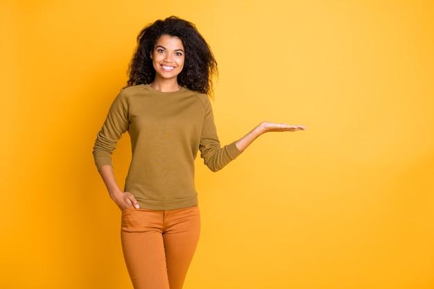 Foto van mooie donkere huid verkoper dame bedrijf nieuw product op open palm voorstelt korting prijs dragen casual pullover broek geïsoleerde gele kleur achtergrond