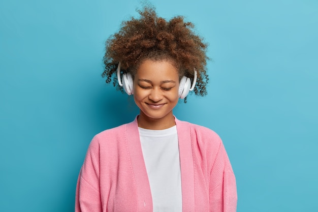 Foto van mooie donkere vrouw heeft een vrolijke bui draagt een koptelefoon en luistert naar aangename muziekstandaards met gesloten ogen gekleed in vrijetijdskleding.