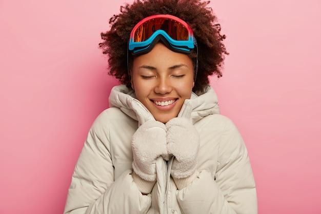 Foto van mooie donkere vrouwelijke snowboarder draagt winterjas en handschoenen, glimlacht van plezier, uiting van gelukkige emoties, geniet van recreatietijd.