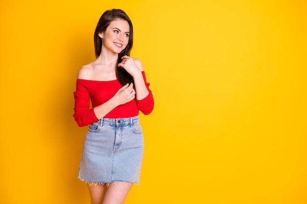 Foto van mooie elegante jonge meid dromerige blik lege ruimte spelen haar flirt aantrekken man dragen shirt onbedekte schouders denim minirok geïsoleerde levendige gele kleur achtergrond