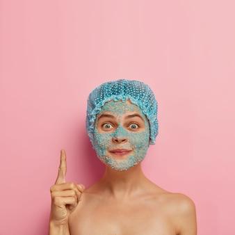 Foto van mooie europese vrouw heeft blauwe spa-zoutkorrels op het gezicht, draagt een waterdichte hoofddeksel, wijst met wijsvinger naar boven