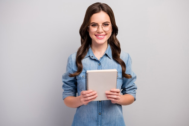 Foto van mooie freelancer dame houd papier planner ijverige betrouwbare student toothy glimlachen slijtage specs casual jeans denim overhemd geïsoleerde grijze kleur