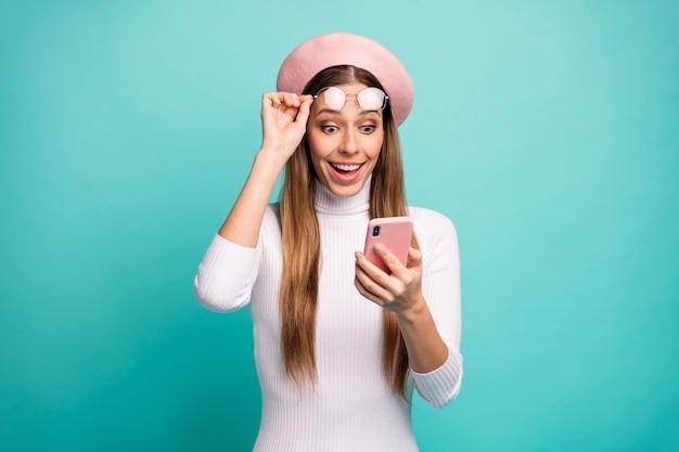 Foto van mooie gekke geschokte dame houdt telefoon koele internetverbinding opstijgen trendy bril draag specificaties roze baret pet witte coltrui geïsoleerde groenblauw kleur achtergrond