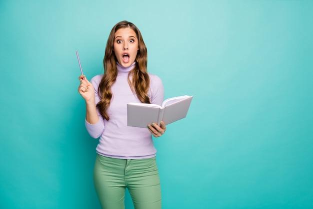 Foto van mooie gekke opgewonden golvende dame houd planner heb creatief bedrijfsidee houd potlood open mond draag lila trui groene broek geïsoleerde groenblauw pastelkleur