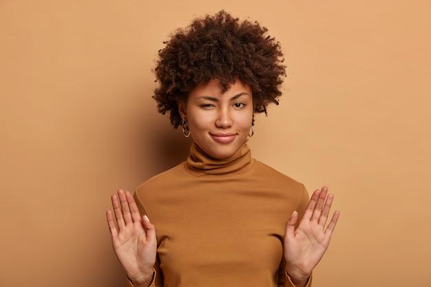 Foto van mooie gekrulde vrouw weigert vreemd aanbod, houdt de handpalmen naar voren, heeft een mysterieuze uitdrukking, draagt bruine poloneck, weigert uitnodiging, weigert verontschuldiging
