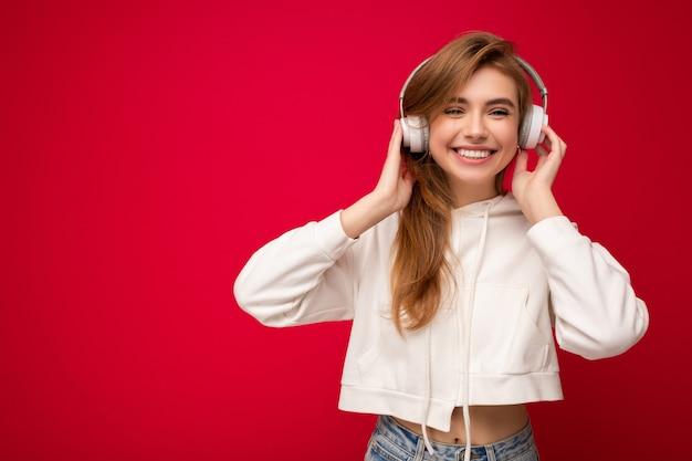 Foto van mooie gelukkige glimlachende jonge blonde vrouw die witte hoodie draagt die over kleurrijk wordt geïsoleerd