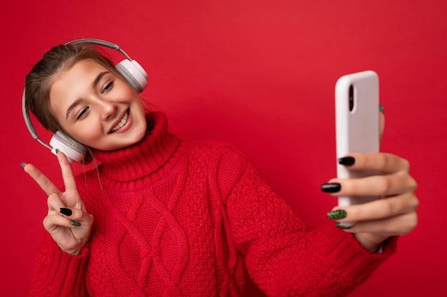 Foto van mooie gelukkige jonge donkerbruine vrouw die rode sweater draagt die over rode muur wordt geïsoleerd als achtergrond