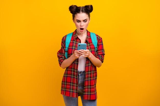 Foto van mooie geschokt student dame houdt telefoon open mond