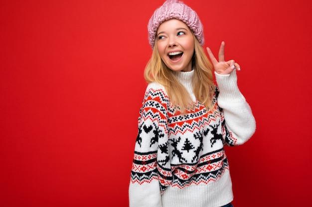 Foto van mooie glimlachende jonge blonde vrouw, gekleed in warme gebreide muts en warme winter trui staande geïsoleerd op rode achtergrond