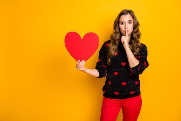 Foto van mooie golvende dame amour houdt grote papieren hart vinger op lippen met creatief idee datum uitnodiging slijtage harten patroon trui rode broek
