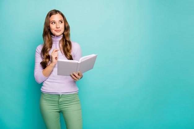 Foto van mooie golvende dame hold planner schrijf creatief bedrijfsidee in dagboek opzoeken lege ruimte diep denken dragen lila trui groene broek geïsoleerd groenblauw pastelkleur