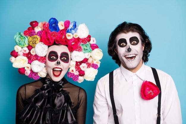 Foto van mooie griezelige paar man dame verrast open mond hebben korting op een dag weer tot leven dragen zwarte jurk dood kostuum rozen hoofdband bretels geïsoleerde blauwe kleur achtergrond