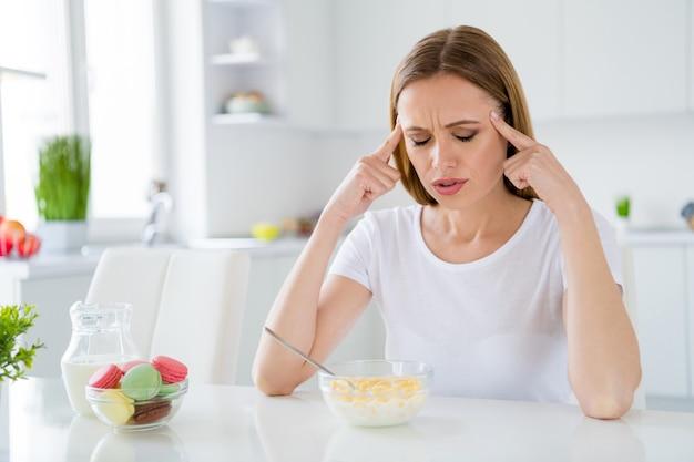 Foto van mooie huisvrouw die tempels houdt die lijden aan vreselijke pijn kan geen melk eten, ontbijt cornflakes hebben een kater na avondfeest zittend tafel wit licht keuken binnenshuis