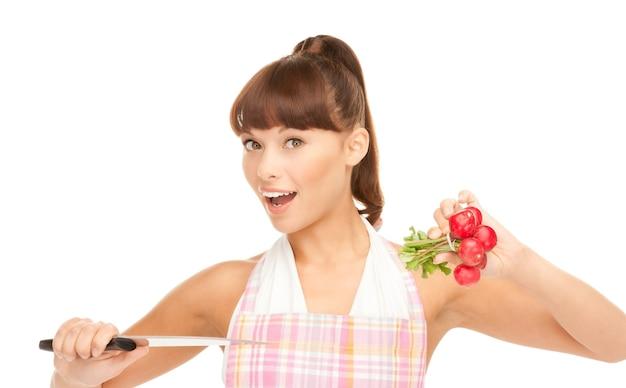 Foto van mooie huisvrouw met groot mes en radijs
