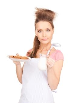 Foto van mooie huisvrouw met melk en koekjes
