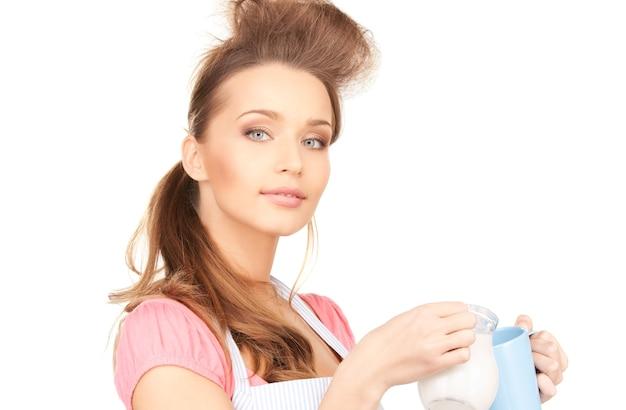 Foto van mooie huisvrouw met melk en mok