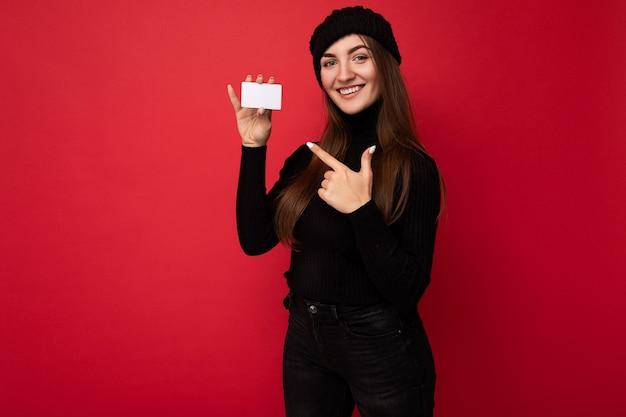 Foto van mooie jonge brunette vrouw met zwarte trui en hoed geïsoleerd op rode achtergrond met creditcard kijkend naar camera en wijzende vinger naar plastic kaart
