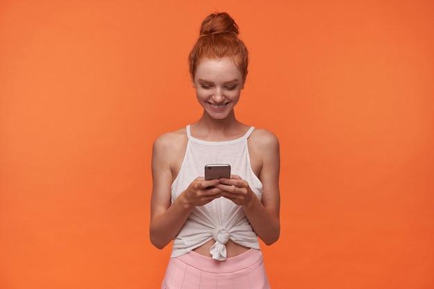 Foto van mooie jonge dame met foxy broodje kapsel dragen witte top en roze rok, smartphone in handen houden en scherm gelukkig kijken, positief glimlachend terwijl staande over oranje achtergrond