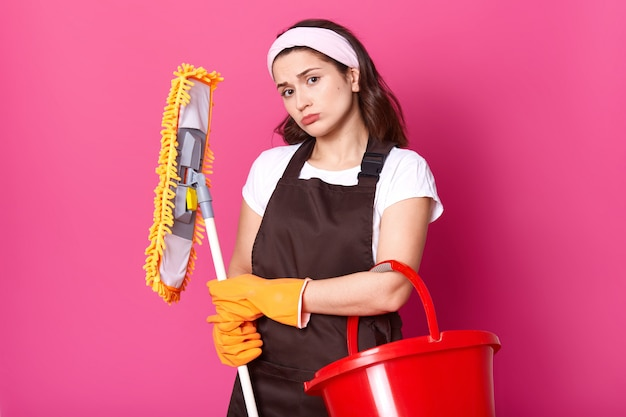 Foto van mooie jonge huisvrouw met pruilende lippen, wil haar huis niet schoonmaken in plaats van te gaan daten, boos op haar huishoudelijke taken, heeft een gele dweil en een rode emmer. studio-opname.