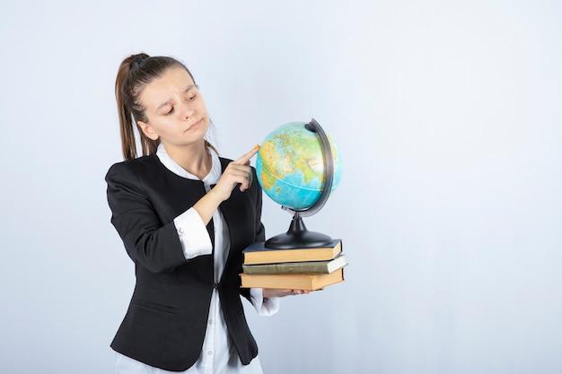 Foto van mooie jonge leraar met boeken die op wereldbol op wit richten.