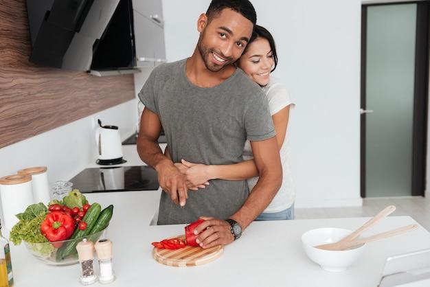 Foto van mooie jonge paar in de keuken knuffelen tijdens het koken.