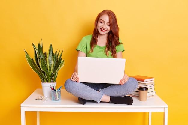Foto van mooie jonge roodharige student zittend op een witte tafel met lap top op knieën, terloops gekleed, online werken of leerafstand.