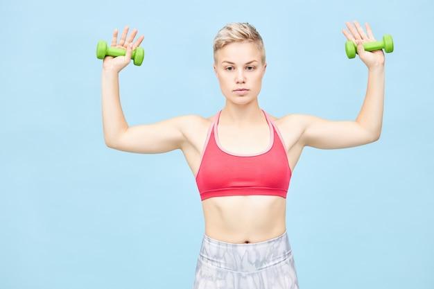 Foto van mooie jonge sportieve vrouw met jongensachtig haar die fysieke oefeningen doet, armen zijwaarts houdt met twee groene halters in haar handen, biceps en schouderspieren trainen