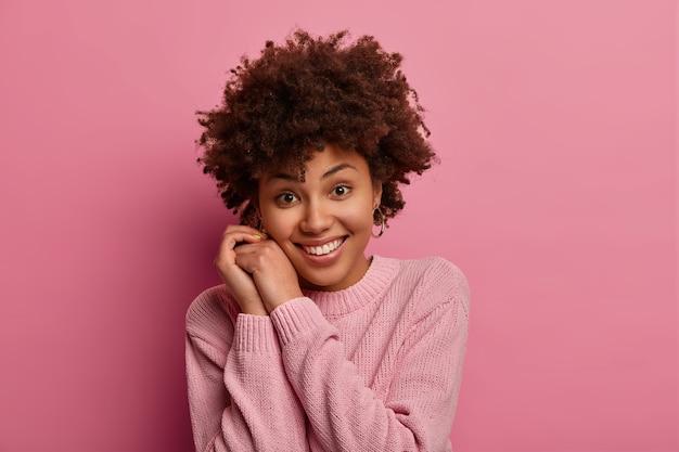 Foto van mooie jonge tedere vrouw met afrohaar glimlacht zachtjes, houdt handen in de buurt van gezicht, kijkt direct, draagt casual trui, hoort iets goeds, poseert tegen roze muur