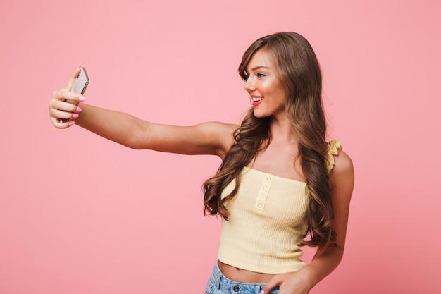 Foto van mooie jonge vrouw 20s met lang bruin haar, gekleed in zomerkleding glimlachend terwijl het nemen van selfie op mobiele telefoon, geïsoleerd op roze achtergrond