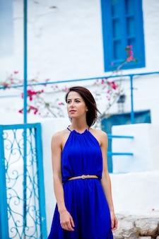 Foto van mooie jonge vrouw die zich op de treden dichtbij het huis in griekenland bevindt