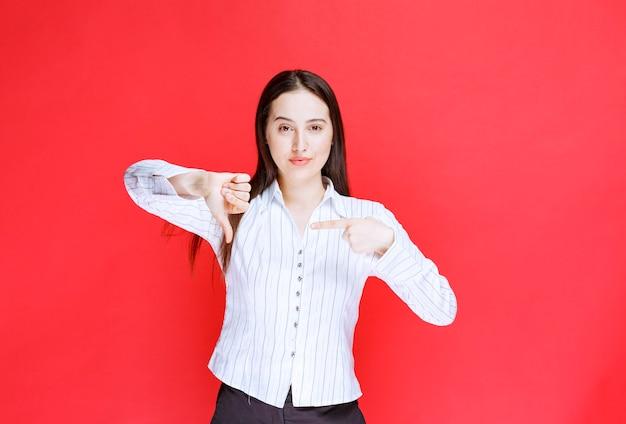 Foto van mooie jonge vrouw in formele outfit met duimen naar beneden.