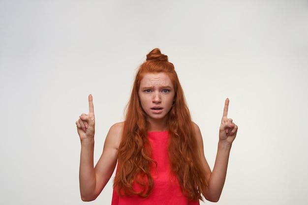 Foto van mooie jonge vrouw met foxy golvend haar die geen make-up dragen die zich voordeed op witte achtergrond, op zoek naar camera met verward gezicht en wijsvingers verhogen, fronsend met gerimpeld voorhoofd