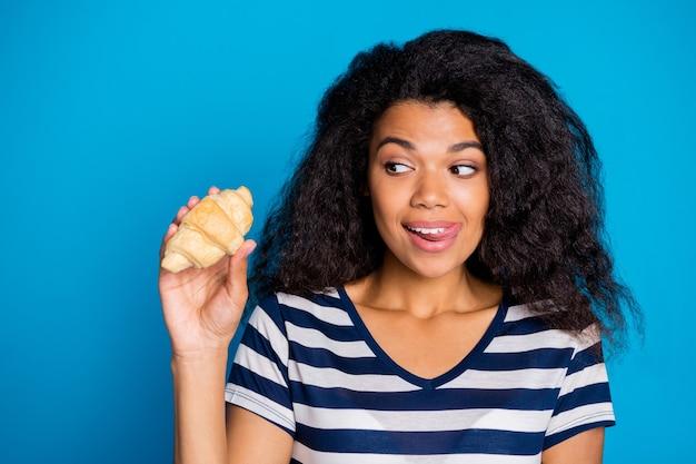 Foto van mooie jongere in verleiding likken haar bovenlip met croissant