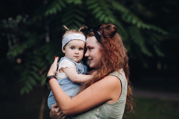 Foto van mooie kleine baby gaat wandelen in het park met haar moeder en ze is geïnteresseerd