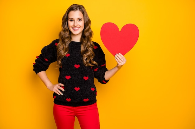 Foto van mooie krullende dame amour die groot papier hart houden demonstrerend creatief idee briefkaart datum uitnodiging slijtage harten patroon trui rode broek