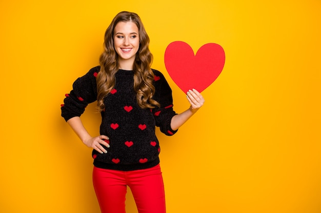 Foto van mooie krullende dame amour romantiek humeur met groot papieren hart met creatief idee briefkaart slijtage harten patroon trui rode broek