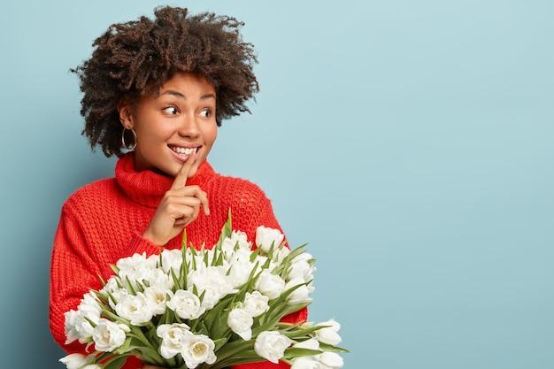 Foto van mooie krullende vrouw kijkt vreugdevol opzij, maakt stilte-gebaar, gekleed in rode winterse trui, vertelt geheim wie witte tulpen gaf, roddels met vriend, geïsoleerd op blauw. dame houdt bloemen vast