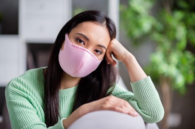 Foto van mooie maar trieste corona-virus zieke patiënt huiselijke aziatische dame zittend op de bank leunend hoofd op hand humeurig vermist wandelingen buiten buiten moet zichzelf isoleren blijf binnen thuis