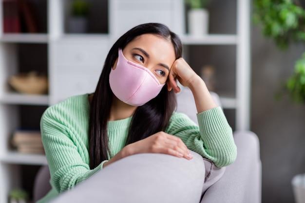 Foto van mooie maar verdrietige corona-virus zieke patiënt huiselijke aziatische dame zittend op de bank kijk dromerig raam ontbreekt naar buiten gaan moet zichzelf isoleren blijf binnen thuis