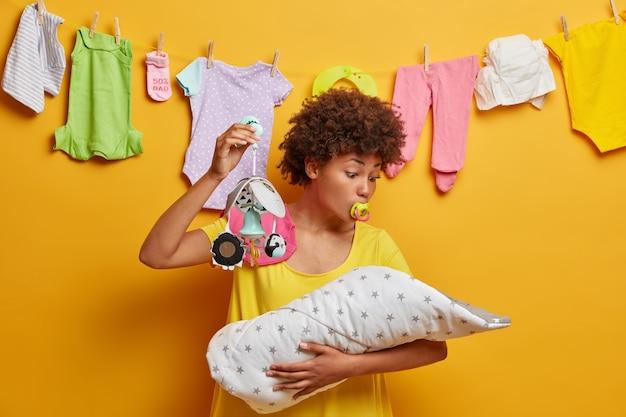 Foto van mooie mama kijkt naar baby en probeert ondeugend pasgeboren te kalmeren, toont mobiel en zuigt tepel, zuigeling zuigt, speelt met dochtertje, staat over gele muur met gewassen kleren