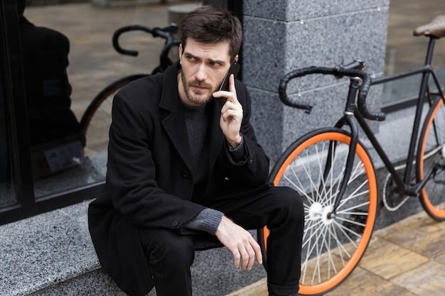 Foto van mooie man 20s praten op mobiele telefoon, zittend buiten met fiets