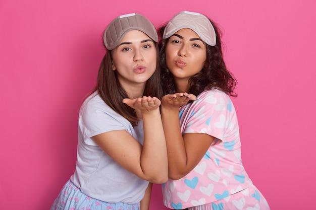 Foto van mooie meisjes die in pyjama's stellen. studio die van twee vrienden is ontsproten die zich op roze bevinden