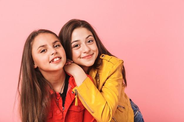 Foto van mooie meisjes in casual knuffelen samen, geïsoleerd over rode muur
