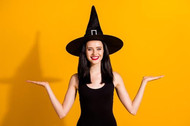 Foto van mooie mooie jonge goochelaar dame glanzende glimlach houd lege ruimte presenteren producten even goede kwaliteit dragen zwarte tovenaar hoofddeksel jurk geïsoleerde felgele kleur achtergrond
