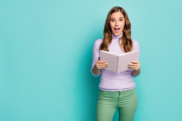 Foto van mooie opgewonden golvende dame houd planner dagboek boek open mond lees wetenschappelijke feiten niet geloven ogen dragen lila trui groene broek geïsoleerde groenblauw pastelkleur